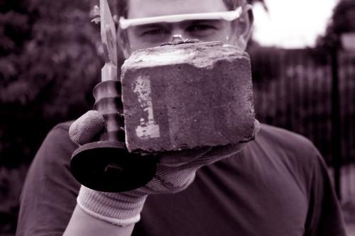 Jamie Robinson (KHOM) with brick number 1, 18 Aug 2014. Photo: Pam Van-Damned Visuals.